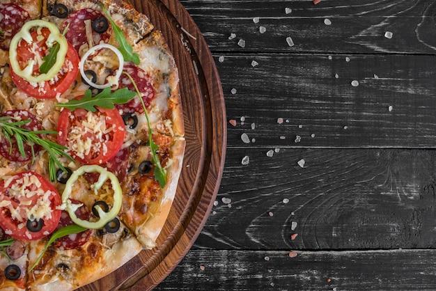 Pizza di verdure, funghi e pomodori su un fondo di legno nero.
