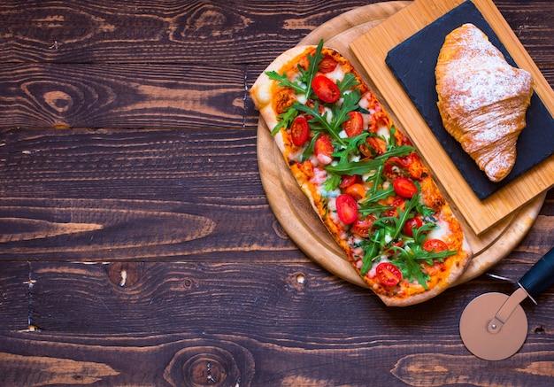 Pizza domestica domestica fresca con rucola di pomodori e mozzarell