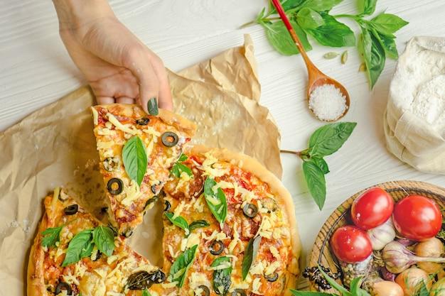 Pizza e mano da vicino su sfondo bianco