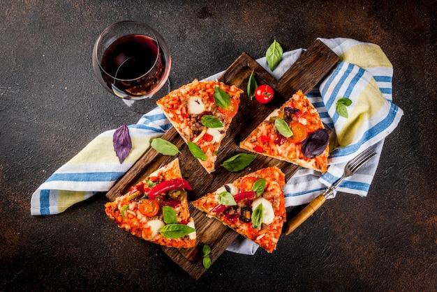 Pizza e vino rosso su sfondo scuro