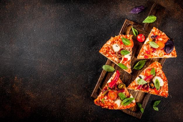 Pizza e vino rosso sulla vista superiore del fondo scuro