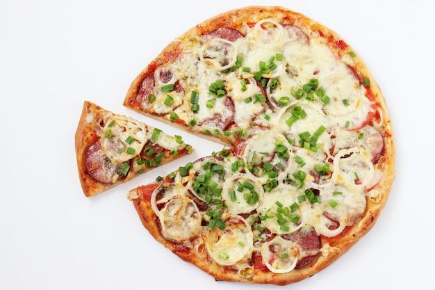 Pizza fatta in casa con mozzarella e salame, vista dall'alto, una fetta di pizza tagliata