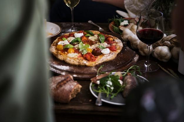 Pizza fatta in casa per cena con vino rosso