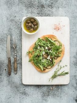 Pizza fatta in casa rustica con melanzane, formaggio, olive e rucola sul bordo di servizio in legno bianco