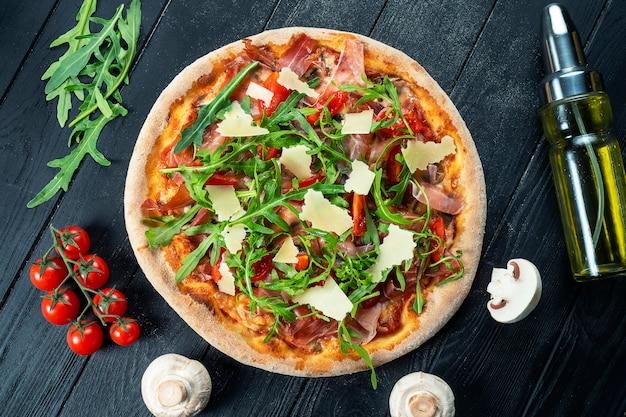 Pizza fresca fatta in casa con rucola, parmigiano e pomodorini su un legno nero con spazio di copia.