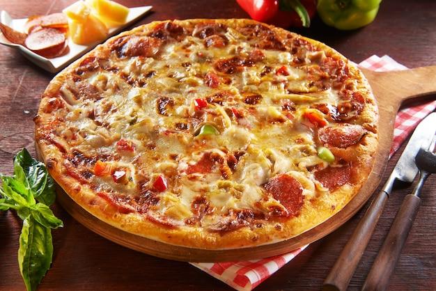 Pizza fresca sulla tavola di legno con gli ingredienti