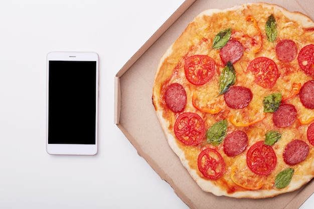 Pizza in scatola e smartphone con lo schermo in bianco sulla tavola bianca, vista superiore delle merguez deliziose isolate sopra la superficie della luce. telefono cellulare moderno vicino alla scatola con pizza. copia spazio per pubblicità.