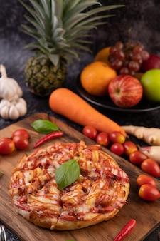 Pizza in un vassoio di legno con pomodori peperoncino e basilico.