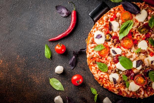 Pizza italiana a bordo griglia con vari ingredienti su sfondo scuro
