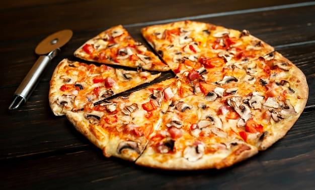Pizza italiana con funghi, pomodori e formaggio su legno