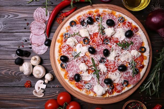 Pizza italiana con i migliori prodotti, con pomodori, mozzarella, funghi e olive, salame