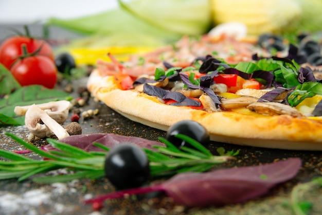Pizza italiana con mozzarella, olive nere, prosciutto e pomodori