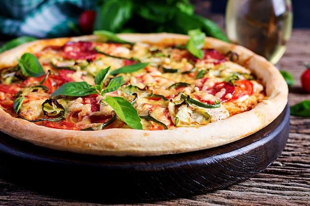Pizza italiana con pollo, salame, zucchine, pomodori ed erbe sul tavolo di legno d'epoca. cucina italiana