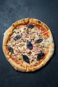Pizza italiana con prosciutto, funghi e basilico.