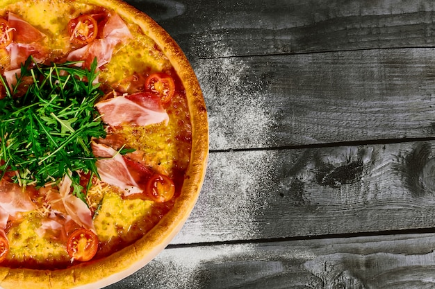 Pizza italiana con prosciutto, pomodori ed erbe su un tavolo di legno