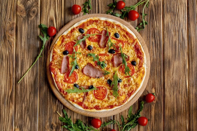Pizza italiana con prosciutto, pomodori, olive e basilico sul tavolo di legno.