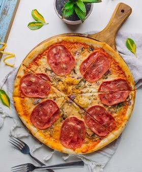 Pizza italiana con salame, aneto, funghi, cipolla rossa, formaggio su sfondo bianco