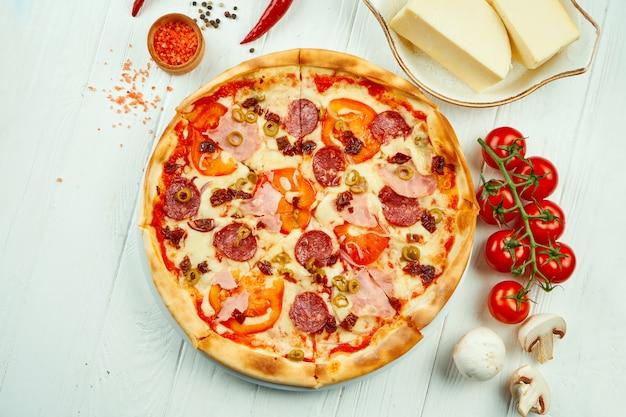 Pizza italiana con salame, prosciutto e olive in una composizione con ingredienti