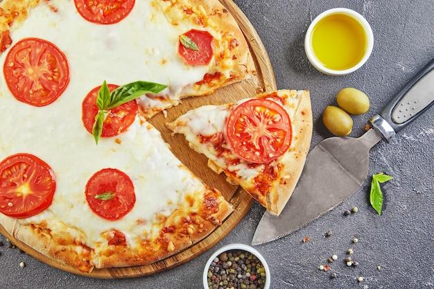 Pizza italiana e ingredienti per cucinare su uno sfondo di cemento nero copia spazio per il testo.