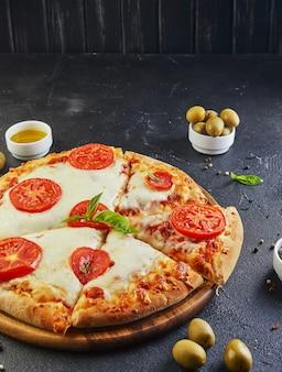 Pizza italiana e ingredienti per cucinare su uno sfondo nero di cemento vista laterale