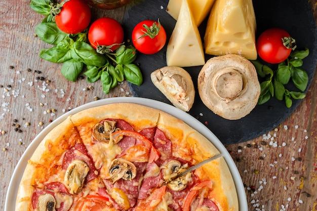 Pizza italiana e ingredienti su legno, vista dall'alto