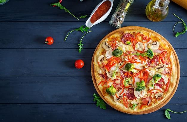 Pizza italiana fresca con filetto di pollo, funghi, prosciutto, salame, pomodori, broccoli, formaggio su sfondo nero.