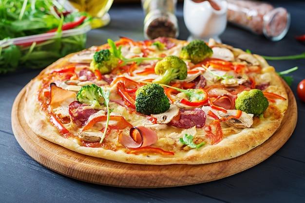 Pizza italiana fresca con filetto di pollo, funghi, prosciutto, salame, pomodori, broccoli, formaggio sulla superficie nera. cibo italiano.