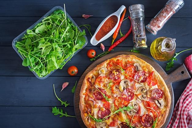Pizza italiana fresca con filetto di pollo, funghi, prosciutto, salame, pomodori, formaggio su una superficie nera. cibo italiano. vista dall'alto