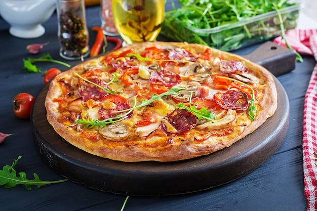 Pizza italiana fresca con filetto di pollo, funghi, prosciutto, salame, pomodori, formaggio su una superficie nera. cibo italiano.
