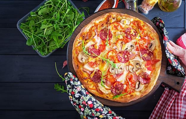 Pizza italiana fresca con filetto di pollo, funghi, prosciutto, salame, pomodori, formaggio su uno sfondo nero nelle mani.