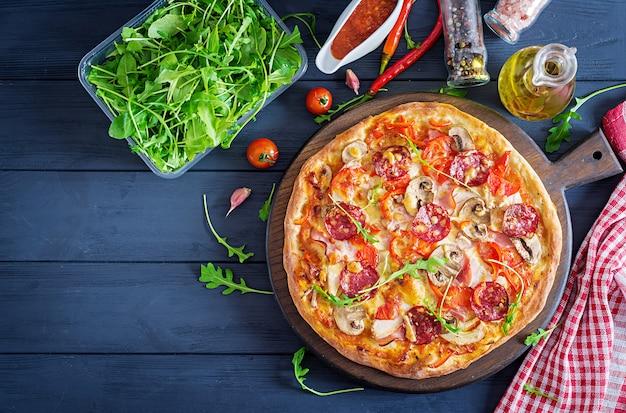 Pizza italiana fresca con filetto di pollo, funghi, prosciutto, salame, pomodori, formaggio su uno sfondo nero.