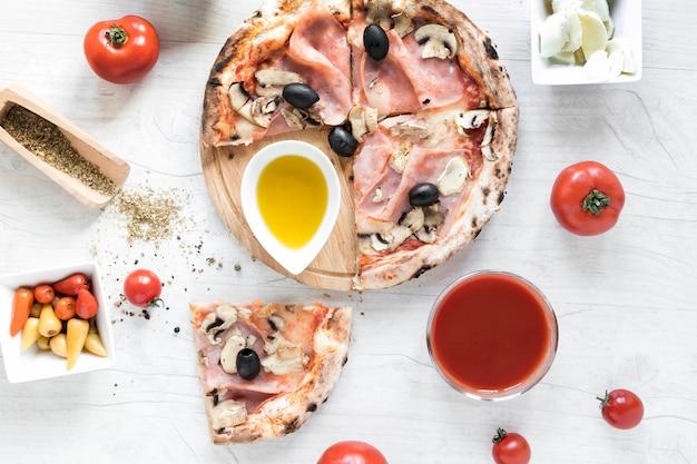 Pizza italiana fresca con ingredienti sul tavolo di legno bianco