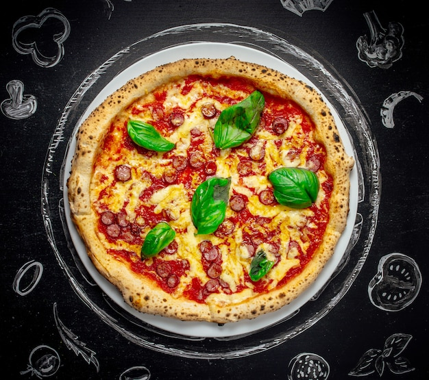 Pizza italiana saporita con basilico su fondo di pietra nero, vista superiore.