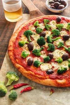 Pizza italiana sulla tavola di legno con ingredienti