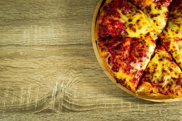 Pizza margarita con mozzarella su un tavolo di legno