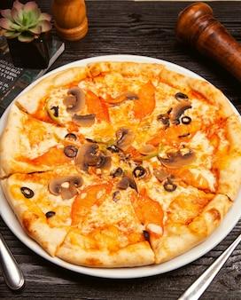 Pizza margarita con olive nere, funghi, salsa di pomodoro, fette di pomodoro e parmigiano sul piatto bianco.