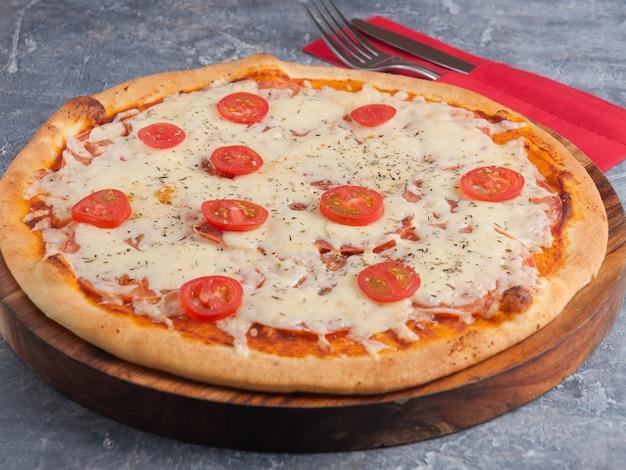 Pizza margarita con pomodorini su una tavola di legno