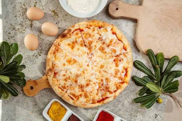 Pizza margarita e uova sul tavolo