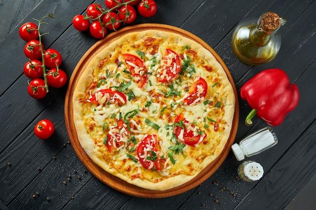 Pizza margherita al forno con pomodori, mozzarella e salsa rossa su una superficie di legno in una composizione con ingredienti