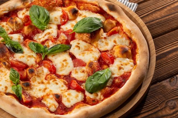 Pizza margherita su fondo di legno, vista dall'alto. volantino e poster per ristoranti o pizzerie