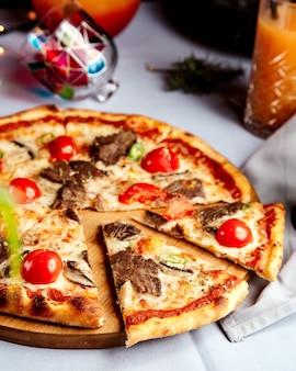 Pizza mista con pezzi di carne e pomodoro