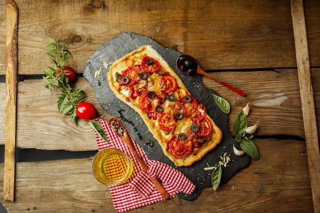 Pizza mista con pollo, pepe, olive, cipolla, basilico su tagliere