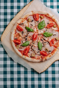 Pizza napoletana con funghi, formaggio, rucola, basilico, pomodori cosparsi di formaggio