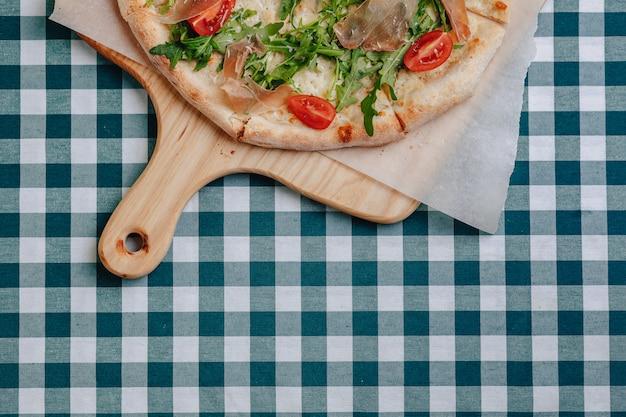 Pizza napoletana con salame, rucola, pomodori cosparsi di formaggio su una tavola di legno su una tovaglia in una cella