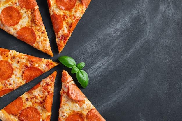 Pizza peperoni saporita su fondo concreto nero
