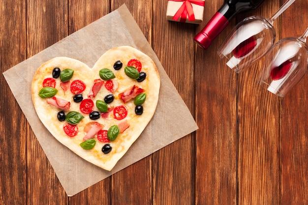 Pizza piatta a forma di cuore con vino
