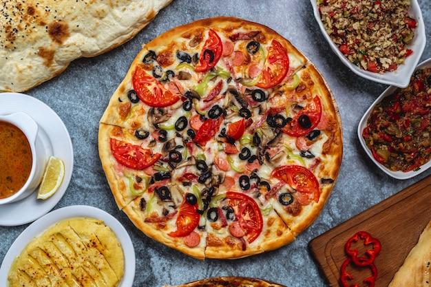 Pizza salsicce vista dall'alto con pomodoro peperone e formaggio olive nere sul tavolo