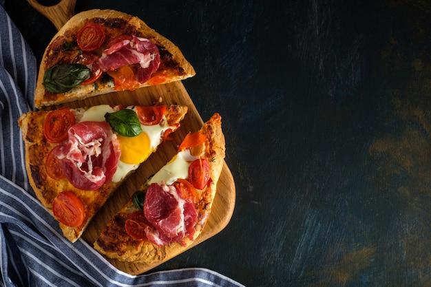 Pizza saporita casalinga affettata con pancetta affumicata, uovo, formaggio, pomodori e basilico su oscurità