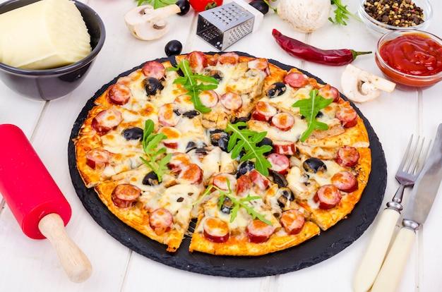 Pizza saporita con salame, funghi e olive su fondo di legno.