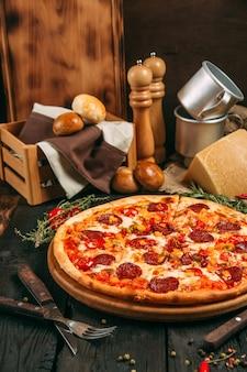 Pizza saporita deliziosa di vista laterale con le merguez e pepe sul bordo nero sui precedenti di legno scuri, verticali